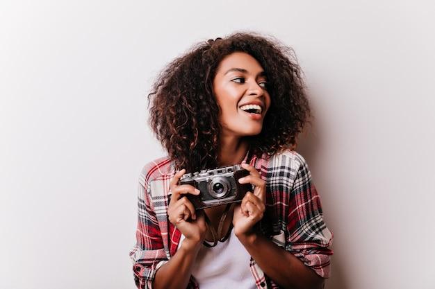 Cieszę się, że strzelanka miotająca. marzycielska afican kobieta w kraciastej koszuli trzymając aparat.