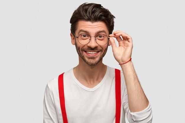 Cieszę się, że stylowy hipster z szerokim uśmiechem, nosi okulary, biały swobodny sweter i czerwone szelki