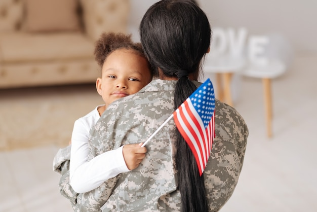 Cieszę się, że tu jesteś. urocza urocza ładna dziewczyna mocno przytula swoją mamę, witając jej dom i trzymając w dłoni flagę