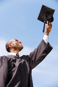 Cieszę się, że ukończyłem studia. niski kąt widzenia szczęśliwego młodego afrykańskiego mężczyzny w sukni ukończenia szkoły, trzymającego deskę zaprawy przeciw błękitnemu niebu