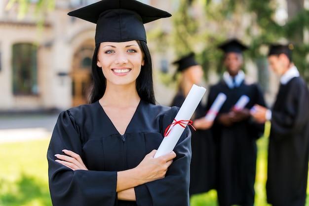 Cieszę się, że ukończyłem studia. szczęśliwa młoda kobieta w sukniach dyplomowych trzymająca dyplom i uśmiechnięta, podczas gdy jej przyjaciele stoją w tle