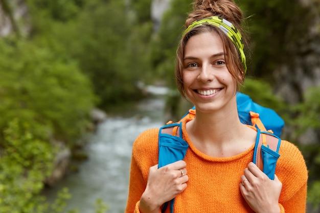 Cieszę się, że uśmiechnięta kobieta o ciemnych włosach nosi opaskę i pomarańczowy sweter