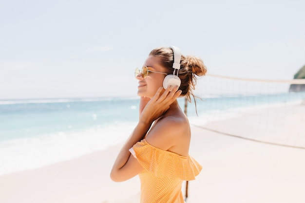Cieszę się, że uśmiechnięta kobieta z opaloną skórą pozuje na plaży z czarującym uśmiechem. plenerowy portret entuzjastycznej dziewczyny z dużymi białymi słuchawkami podczas relaksu na wybrzeżu oceanu.
