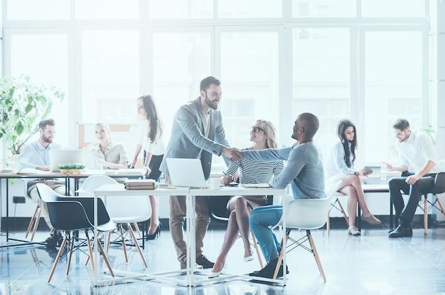 Cieszę się, że widzę cię w zespole! grupa młodych ludzi biznesu pracujących i komunikujących się ze sobą w biurze, podczas gdy dwóch mężczyzn ściska dłonie i uśmiecha się