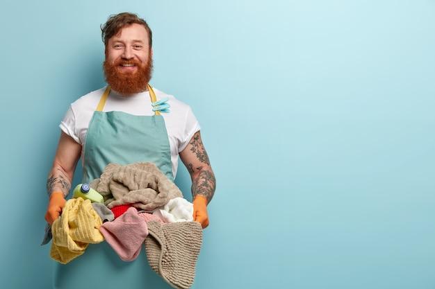 Cieszę się, że zadowolony rudowłosy mężczyzna szczęśliwy kończy prace domowe, trzyma stos świeżego, czystego prania, nosi casualową koszulkę z fartuchem i spinaczami do bielizny