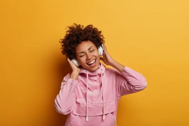 Cieszę się, że zrelaksowana melomanka słucha muzyki przez słuchawki, zamyka oczy i czuje się optymistycznie, ubrana w swobodną bluzę z kapturem, cieszy się przyjemnym dźwiękiem, pozuje na żółtej ścianie. ludzie, czas wolny, szczęście