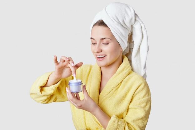 Cieszę się, że zrelaksowana młoda kaukaska kobieta o świeżej zdrowej skórze, zamierzająca nałożyć krem na skórę, ma zabiegi kosmetyczne po prysznicu, na białym. ludzie, piękno, higiena koncepcja.