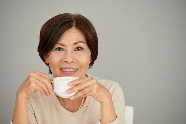 Cieszy się filiżankę herbaty