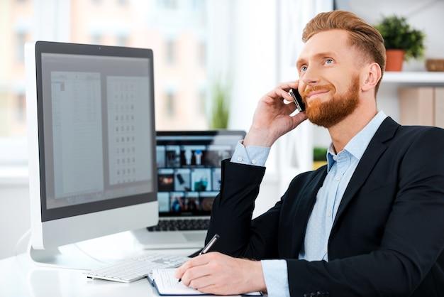 Cieszy się jego pracą. szczęśliwy młody brodaty biznesmen rozmawia przez telefon komórkowy i pisze w notatniku, siedząc w swoim miejscu pracy