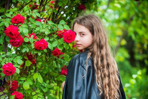 Cieszy się jej dniem. wiosna kwitnące drzewo. letnia natura. kobiece fryzjer moda. mała dziewczynka z kręconymi włosami. mała piękność w białej sukni. dziecko nosić skórzaną kurtkę. dziecko cieszyć się kwiatem róży w parku.