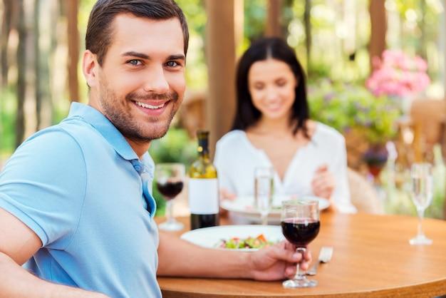 Cieszy się obiadem ze swoją dziewczyną. piękna młoda kochająca para relaksuje się razem w restauracji na świeżym powietrzu, podczas gdy mężczyzna patrzy na kamerę i uśmiecha się