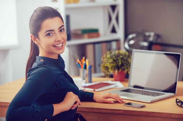 Cieszy się swoim dniem pracy. atrakcyjna młoda kobieta patrząca przez ramię i uśmiechnięta