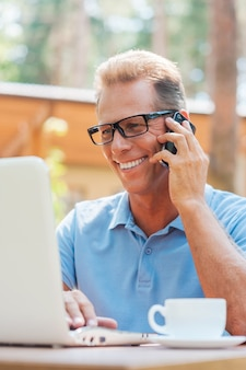 Cieszy Się Swoją Pracą Na świeżym Powietrzu. Szczęśliwy Dojrzały Mężczyzna Pracujący Przy Laptopie I Rozmawiający Przez Telefon Komórkowy Siedząc Przy Stole Na Zewnątrz Z Domem W Tle Premium Zdjęcia
