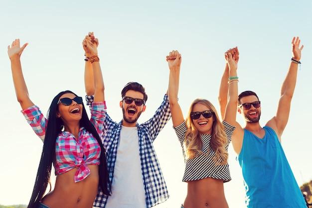 Cieszyć się beztroskim czasem. niski kąt widzenia czterech wesołych młodych ludzi trzymających się za ręce i trzymających uniesione ręce, stojąc na tle nieba