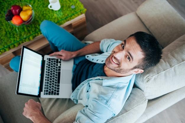 Cieszyć się beztroskim czasem w domu. widok z góry na przystojnego młodego mężczyznę pracującego na laptopie i uśmiechającego się siedząc na kanapie w domu