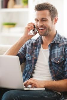 Cieszyć się czasem online. szczęśliwy młody człowiek pracuje na laptopie i rozmawia przez telefon siedząc na kanapie