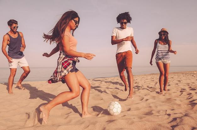 Cieszyć się czasem z najlepszymi przyjaciółmi. grupa wesołych młodych ludzi bawiących się piłką nożną na plaży z morzem w tle