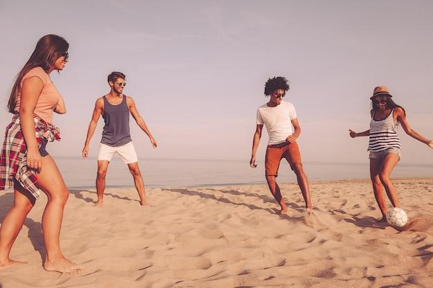Cieszyć się czasem z przyjaciółmi. grupa wesołych młodych ludzi bawiących się piłką nożną na plaży z morzem w tle