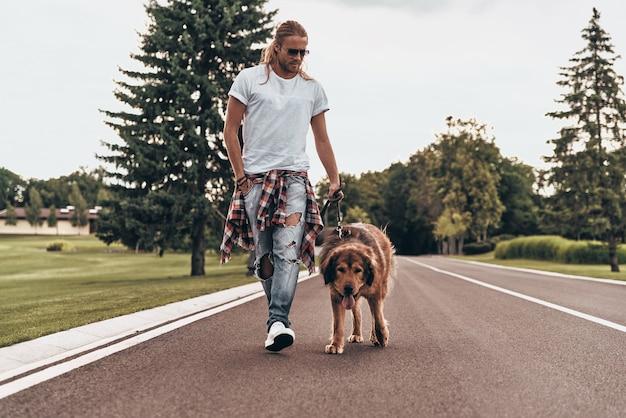Cieszyć się dobrym spacerem. pełna długość przystojnego młodego mężczyzny spacerującego z psem podczas spędzania czasu na świeżym powietrzu
