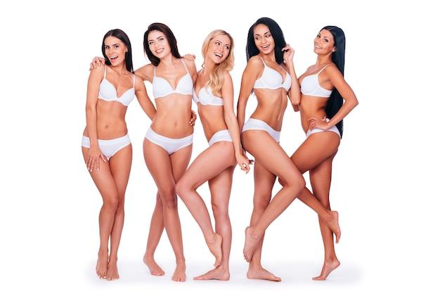 Cieszyć się ich pięknem. pełna długość pięciu pięknych młodych kobiet w bieliźnie, które łączą się ze sobą i uśmiechają, stojąc razem na białym tle