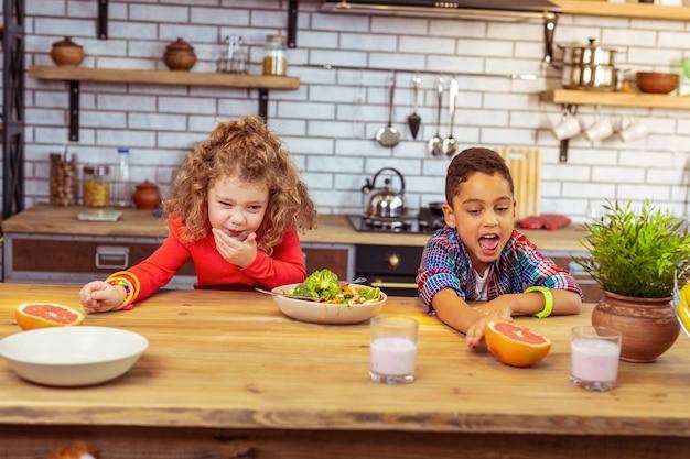 Cieszyć się jedzeniem. przystojny dzieciak z otwartymi ustami patrzący na swój ulubiony owoc