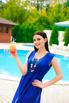 Cieszyć się latem. piękna młoda kobieta pije koktajl podczas gdy relaksujący blisko basenu.