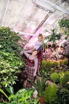 Cieszyć się naturą. widok z góry na dwie miłe, spokojne kobiety cieszące się czasem w szklarni