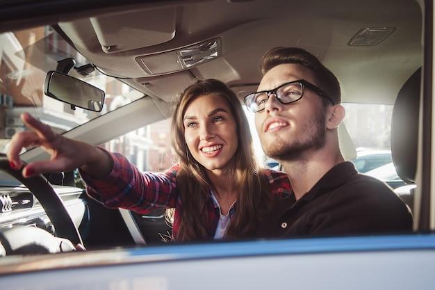 Cieszyć się podróżą. piękna młoda para siedzi na przednim siedzeniu pasażera i uśmiecha się, podczas gdy przystojny mężczyzna prowadzi samochód.