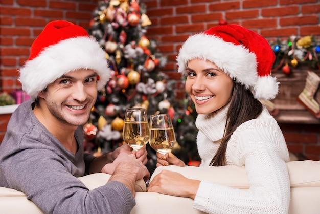 Cieszyć się razem świątecznym czasem. szczęśliwa młoda para kochająca się w santa hat patrząc przez ramiona i uśmiechając się siedząc razem na kanapie i pijąc wino z choinką w tle