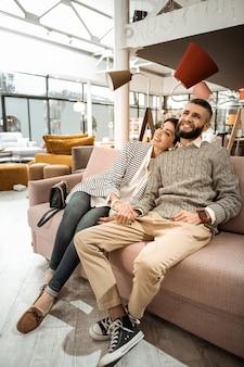 Cieszyć się razem. wspaniała piękna para siedząca z szerokimi uśmiechami na twarzach, zadowolona z wyników zakupów