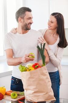 Cieszyć się szczęśliwym i zdrowym życiem razem. piękna młoda para rozpakowuje torbę na zakupy pełną świeżych warzyw i uśmiecha się stojąc razem w kuchni
