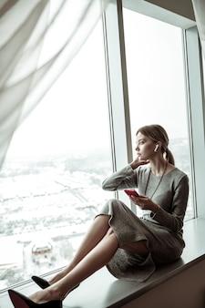 Cieszyć się widokiem. szczupła, stylowa kobieta siedzi przy oknie i podziwiając widok ze swojego mieszkania