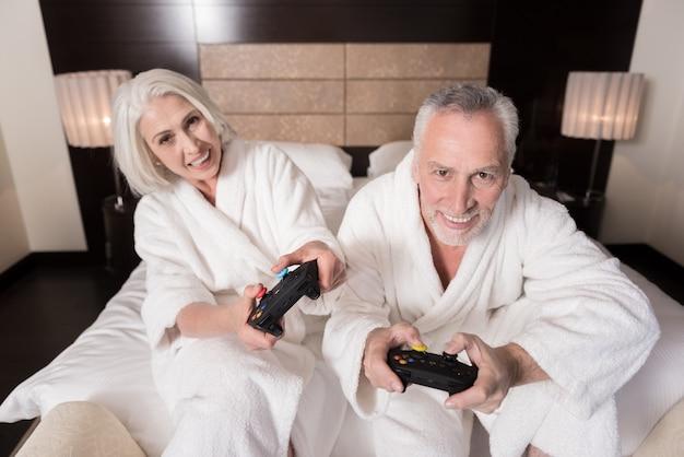 Cieszymy się czasem wolnym. radosna, uśmiechnięta para w wieku trzymająca konsole do gier siedząc na łóżku i wyrażająca radość
