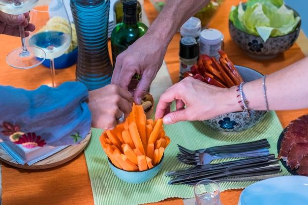Cieszymy się kolacją z przyjaciółmi. widok z góry na grupę ludzi jedzących razem kolację siedzącą przy rustykalnym drewnianym stole - marchewki - stół z trzema rękami biorącymi jedzenie