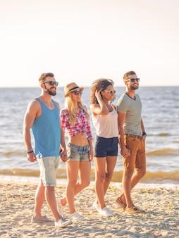 Cieszymy się razem latem. dwie uśmiechnięte młode pary trzymające się za ręce podczas spaceru wzdłuż plaży z morzem w tle