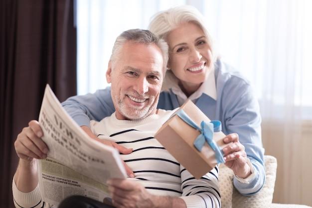 Cieszymy się razem. wesoła uśmiechnięta starsza kobieta trzyma prezent, stojąc w pobliżu sofy i przytulając męża