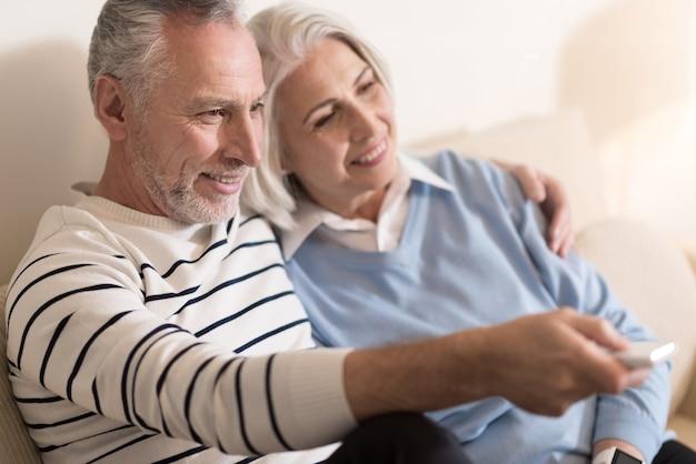 Cieszymy się razem. zachwycona wesoła para w wieku siedzi na kanapie podczas oglądania telewizji i przytulanie się