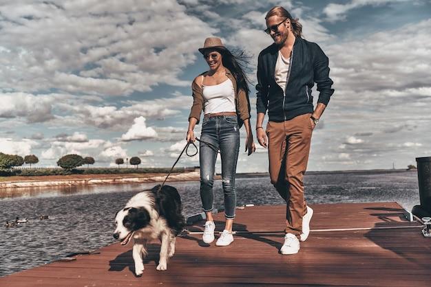 Cieszymy się wspaniałym weekendem. pełna długość pięknej młodej pary spacerującej z psem nad brzegiem rzeki podczas spędzania czasu na świeżym powietrzu