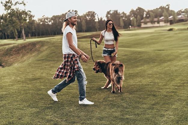 Cieszymy się, że jesteśmy razem. pełna długość pięknej młodej pary bawiącej się z psem podczas spędzania czasu na świeżym powietrzu