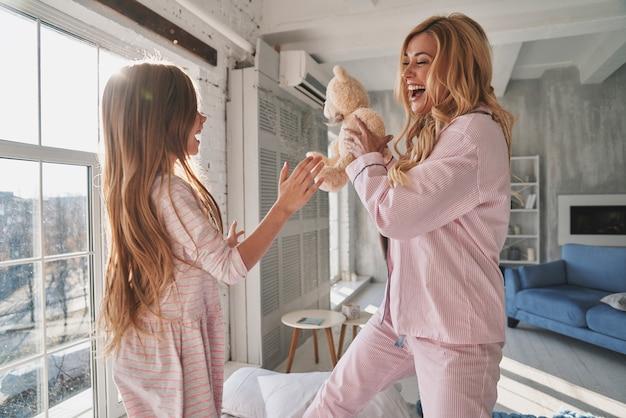 Cieszymy się, że jesteśmy razem. śliczna dziewczynka i jej młoda mama bawią się z misiem i uśmiechają się, spędzając czas w domu
