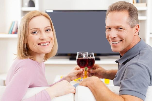 Cieszymy się, że jesteśmy razem. widok z tyłu uśmiechniętej starszej pary siedzącej przed telewizorem i trzymającej kieliszki z czerwonym winem