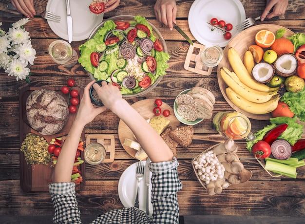 Cieszysz się kolacją z przyjaciółmi. widok z góry grupy osób jedzących obiad razem