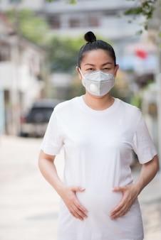 Ciężarna azjatka nosząca maskę zapobiegającą pyłowi pm 2,5 i wirusowi koronowemu, covid 19