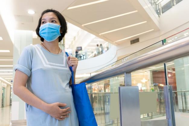 Ciężarna azjatycka kobieta jest ubranym twarzy maskę i wzruszającego brzucha w centrum handlowym. nowa koncepcja normalnego życia.
