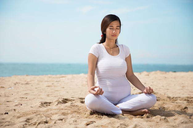 Ciężarna azjatykcia kobieta robi joga w dennym brzeg