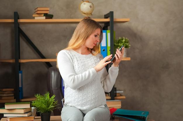 Ciężarna blogerka robi selfie przez telefon. freelancer w ciąży w biurze z telefonem.