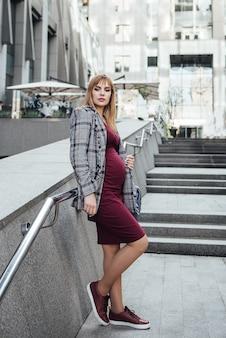 Ciężarna blondynka w bordowej sukience w kształcie i szarej kurtce. w wielkim mieście. szkodliwy dla środowiska. długie włosy. 9 miesięcy w oczekiwaniu. wysokie budynki. urbanizm. szczęście być mamą.