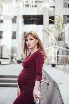 Ciężarna blondynka w kształcie bordowej sukienki. w wielkim mieście. szkodliwy dla środowiska. długie włosy. 9 miesięcy w oczekiwaniu. wysokie budynki. urbanizm. szczęście być mamą.