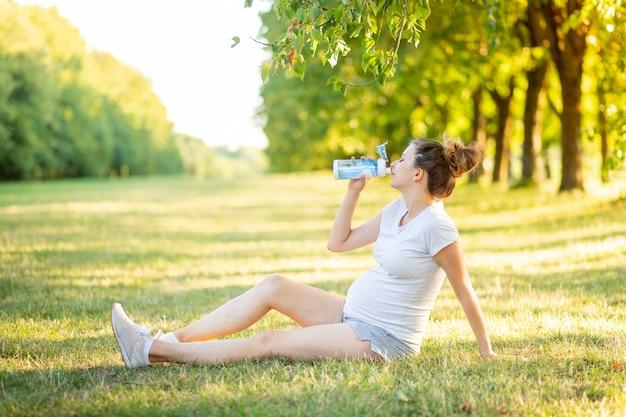 Ciężarna dziewczyna latem uprawia sport na łonie natury, joga dla kobiet w ciąży na świeżym powietrzu