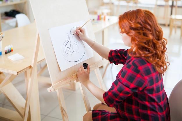 Ciężarna dziewczyna maluje zdjęcie swojej przyszłej rodziny.
